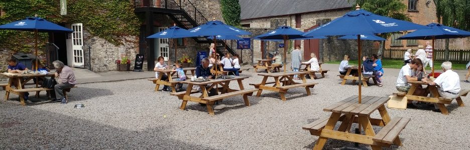 A gravel outdoor area with 8 wooden picnic tables spaced out with blue parasols and people sitting at them at a holiday park cafe