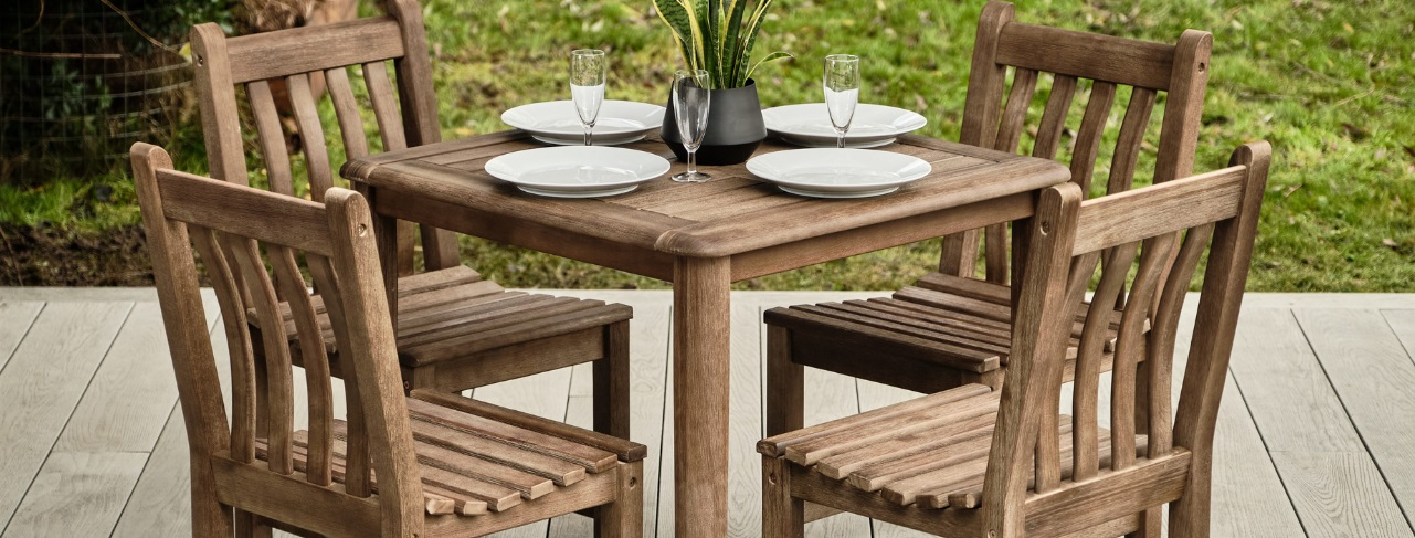 A hard wood square outdoor dining table with four matching chairs around it set with plates and glasses on a grey outdoor deck