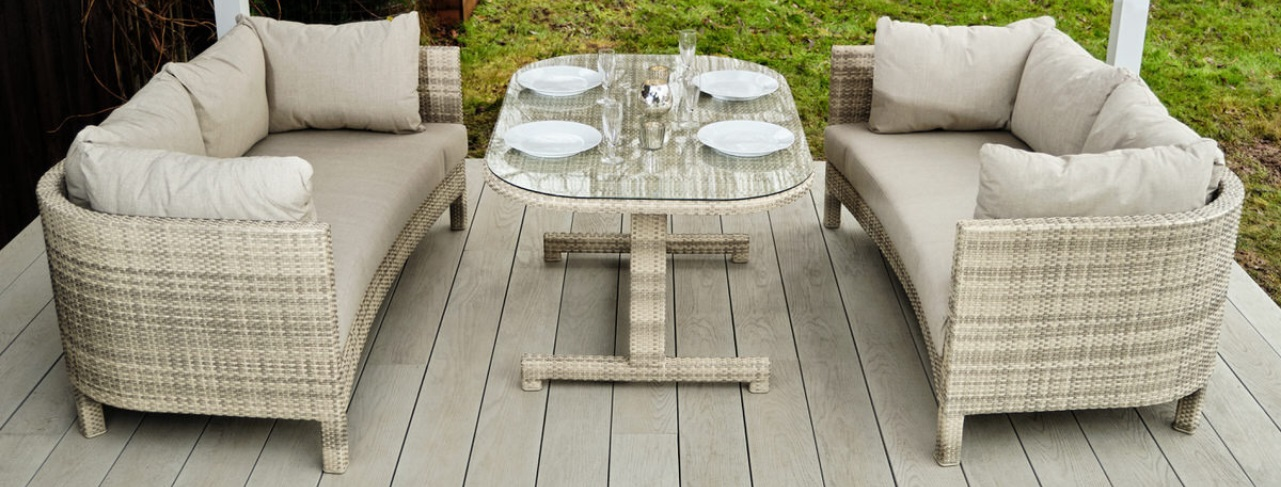 A cream grey weave outdoor rattan sofa and dining table set on a deck