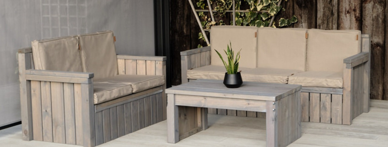 An outdoor wooden 3 seater and 2 seater sofa and a coffee table arranged on a grey outdoor deck