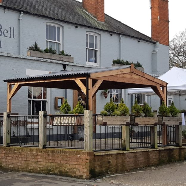 A square wooden gazebo with a waterproof roof on the front patio of a country pub