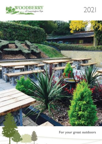 A front cover image of Woodberry 2021 Outdoor Solutions for Hotels showing a hotel patio with rock filled outdoor tables and benches and a colourful shrub border