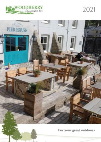 A brochure front Cover of Woodberry Outdoor Solutions for Pubs showing wooden and rock filled outdoor furniture on a brick terrace of a coastal pub