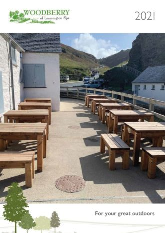 The front cover image of Woodberry 2021 Outdoor Furniture for Tourist Attractions Brochure showing wooden rectangular tables and benches at Tintagel castle