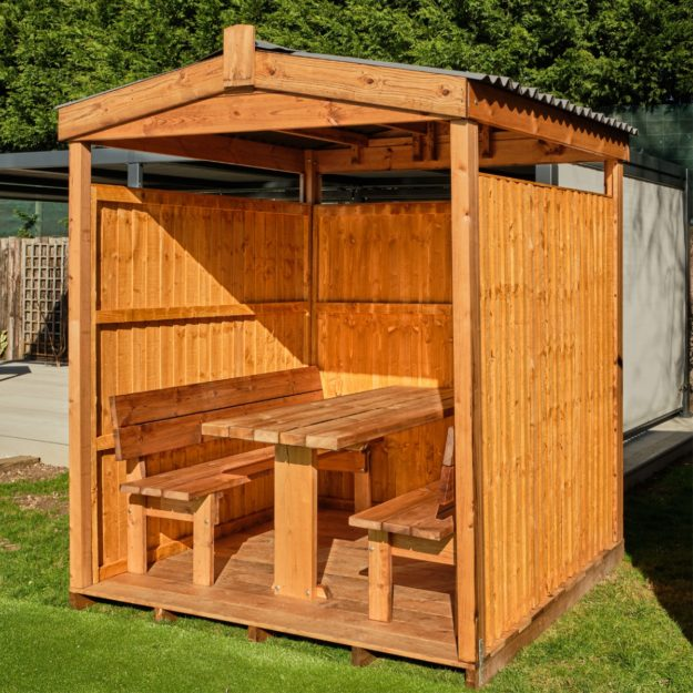 A 6 seater wooden outdoor dining cabin with an apex waterproof roof set on a lawn