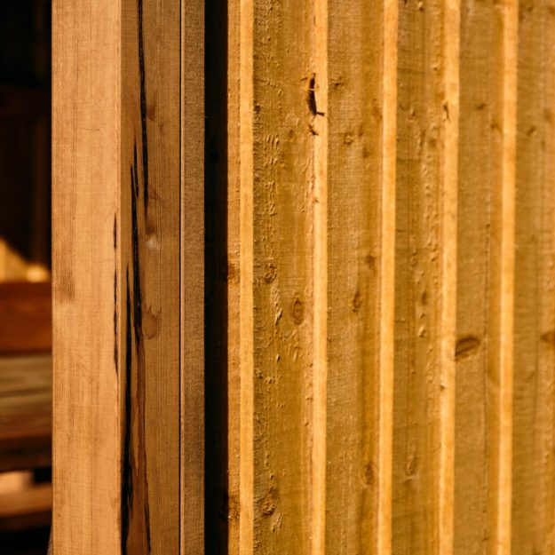 A close up of the wooden wall panel of a budget outdoor dining cabin showing overlapping wooden panels like a fence