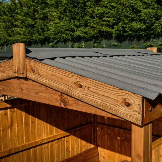 A close up of a wooden outdoor dining cabin pitched apex roof showing corrugated bitumen mix roof panels and wooden apex frame