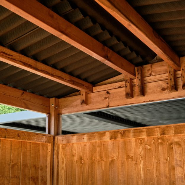 Showing the underside of a corrugated bitumen roof on a budget wooden outdoor dining cabin with wooden roof beams and an apex roof