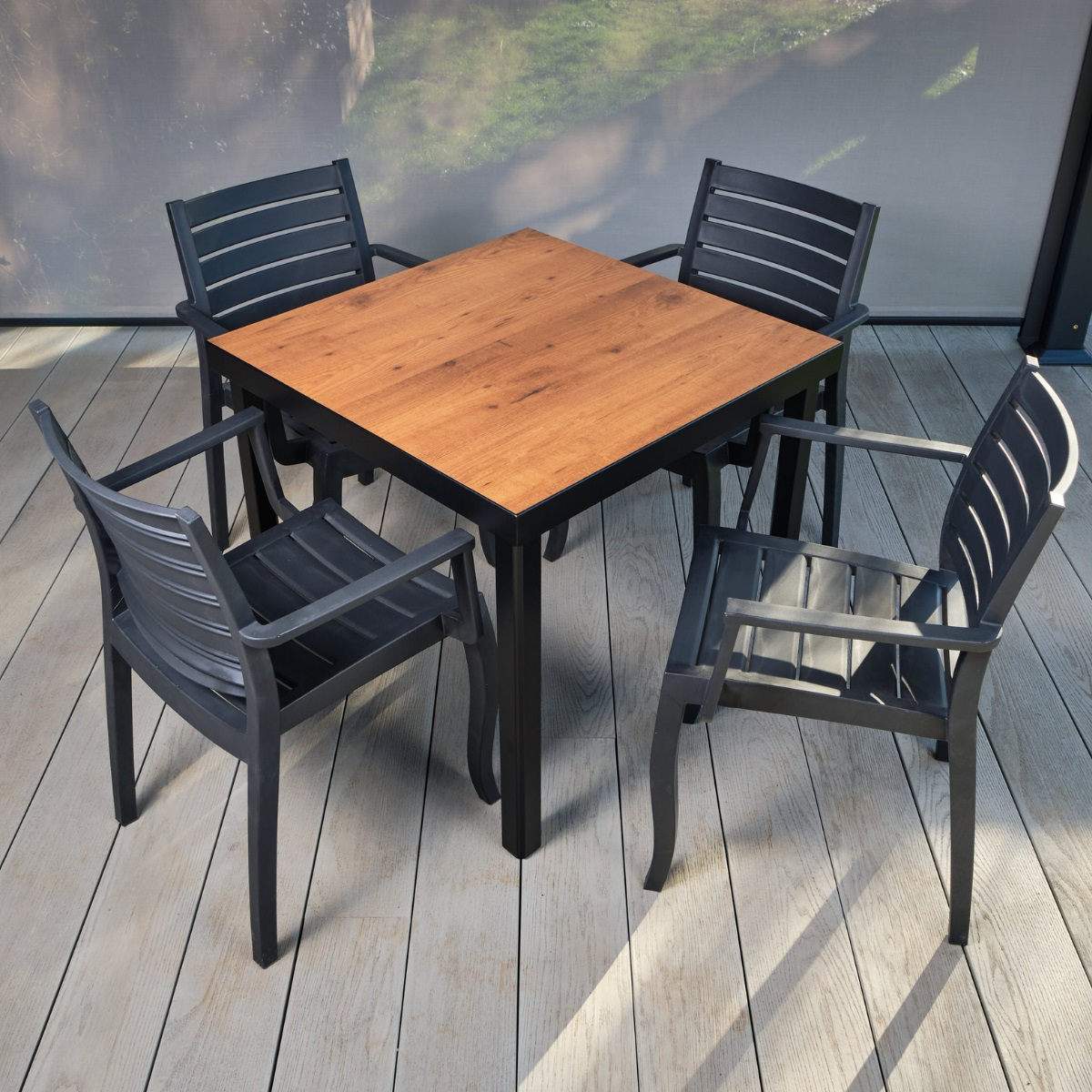 A budget range outdoor dining table and chairs set. Dark grey frames with a laminate wood effect table top. Chairs set round the table on a grey outdoor deck