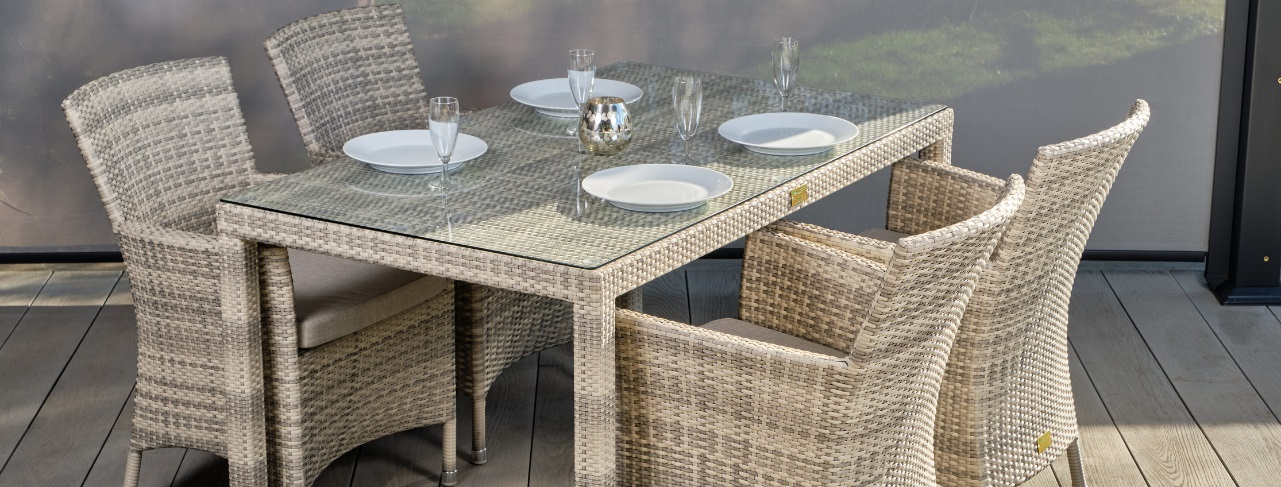 A cream rattan rectangular outdoor dining table and 4 armchairs on a grey outdoor deck