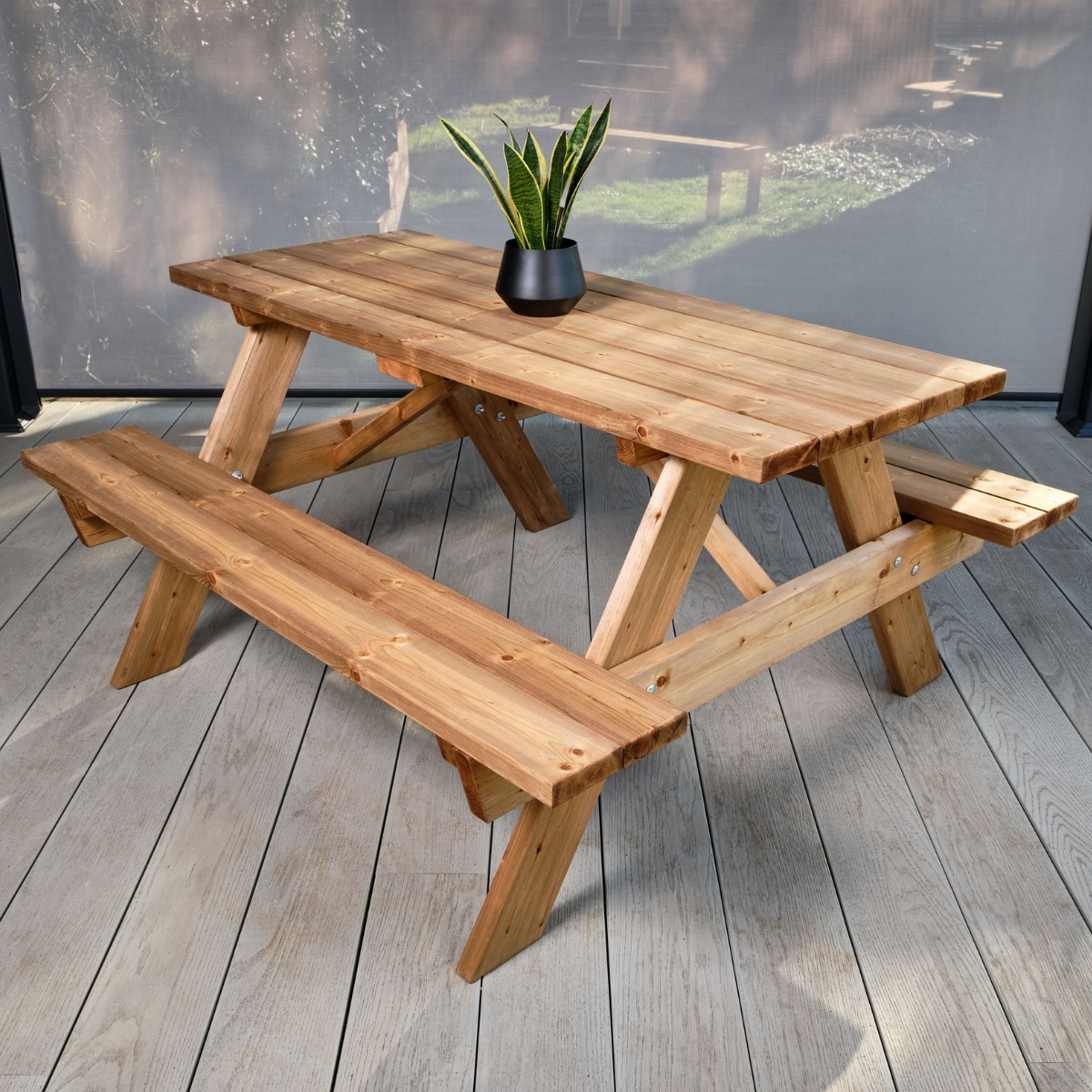 A heavy duty commercial wooden A frame picnic table on a grey deck