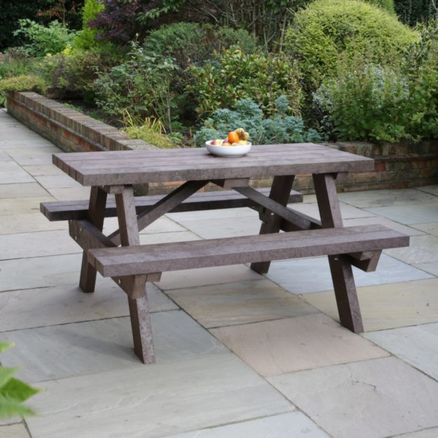 A brown recycled plastic picnic table on a patio