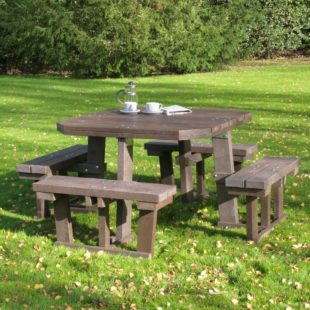A robust square 8 seater picnic table made from recycled plastic on a lawn