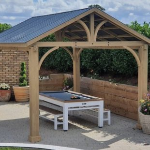 A cedar wood square outdoor gazebo with an apex galvanised steel roof on a patio