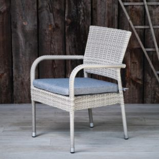 A grey rattan outdoor dining armchair with light grey water resistant outdoor cushion pad side view