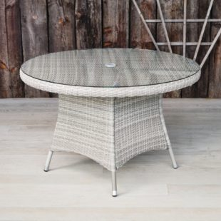 A synthetic grey rattan weave round outdoor dining table with a glass table top on a grey deck